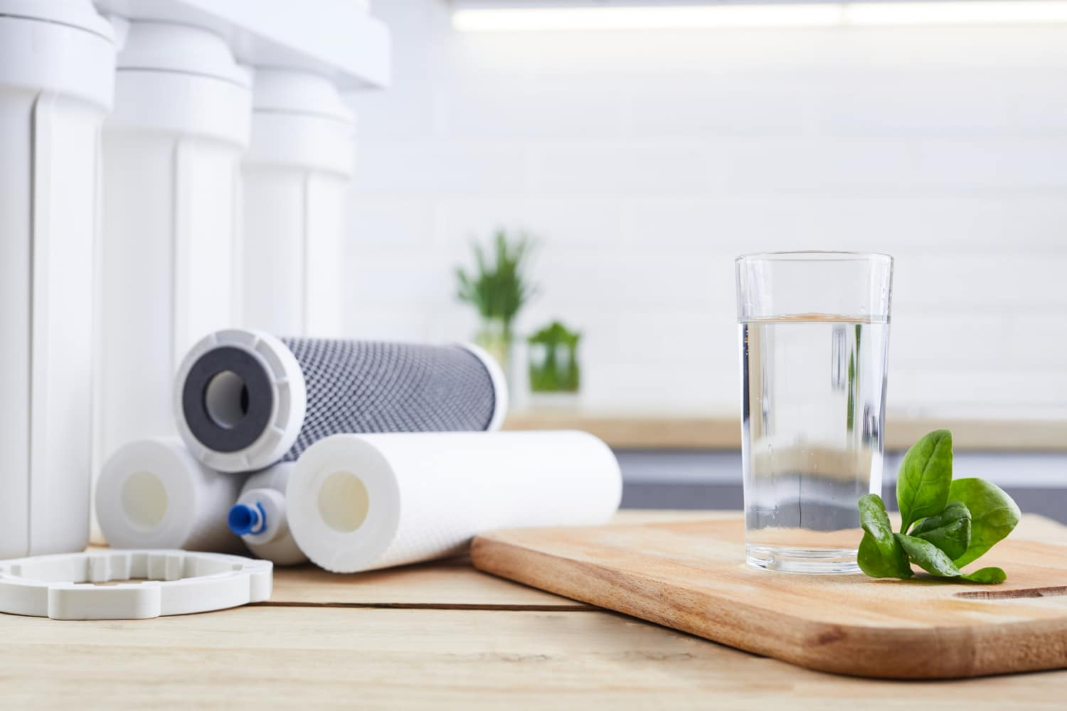 A glass of clean water with osmosis filter, green leaves and cartridges on wooden table in a kitchen interior. Concept Household filtration system.